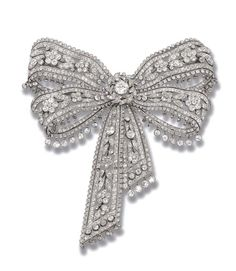 AN ELEGANT BELLE EPOQUE DIAMOND BOW BROOCH, BY CARTIER   The diamond ribbon of floral design with cluster centre and diamond collet fringe, circa 1900, 10.7 cm. wide  By Cartier