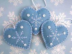 Hecho a mano fieltros adornos de Navidad, copo de nieve azul y blanco de corazones.  Tres luz azul fieltro colgantes corazones, bordadas a mano con un patrón de copo de nieve en blanco, con tres pequeños botones y un lazo para colgar. Altura 7cm  Azul claro con botones y bordado blanco.  Puedes ver más adornos de fieltro corazón aquí; https://www.etsy.com/ie/shop/PuffinPatchwork?ref=hdr_shop_menu&section_id=19324374#policies