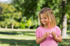 Cute young girl blowing soap bubbles at the park ...  adorable, beautiful, beauty, blonde, blowing, bright, bubbles, casual, caucasian, charming, child, childhood, cute, fair hair, female, freedom, fun, garden, girl, joy, kid, leisure, lifestyle, light hair, looking, outdoors, park, pink, playful, playing, positive, pretty, soap bubbles, standing, summer, trees