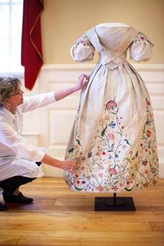 Fashion historian Kimberly Alexander arranges the Elizabeth Bull Colonial wedding dress, which dates back to 1730,  for viewing.