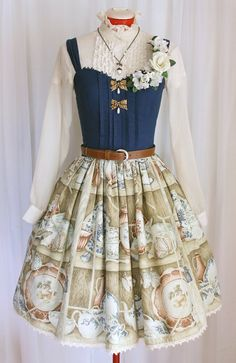 This made to order Jumper-skirt features a darling print of a china cabinet on the skirt. Complete with teacups, saucers, plates, and even a china rabbit. Bodice is made of navy cotton with pin-tucks and matching trim. Bodice is self lined, skirt is lined with silky fabric. It will be