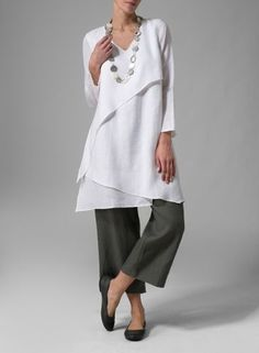 White asymmetrical tunic over grey trousers. Layered tunic by Vivid