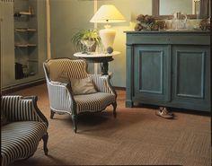 Een vloer bedekt met tapijttegels in het interieur. Deze kokos tegels zorgen voor een landelijke sfeer in deze woonkamer brengt.