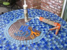 Patio table project - This old table had a stained, scratched and abused glass top.  I purchased one foot square glass mosaic sheets from Home Depot. I cut the squares off the sheet and glued them down to the glass with clear waterproof caulking. Grouted with white grout. Easy!