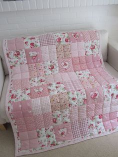 Handmade patchwork quilt with appliqued Hearts 48 x 61 (122cm x 155cm) made from 100% cotton fabric. HAND QUILTED AND HAND FINISHED. Backing fabric - white with flowers. The Quilt has 4oz polyester wadding. Sizes - please note: All items are handmade and therefore dimensions may vary very slightly from those stated. Machine washable on 30 degrees gentle/wool wash - dry flat.