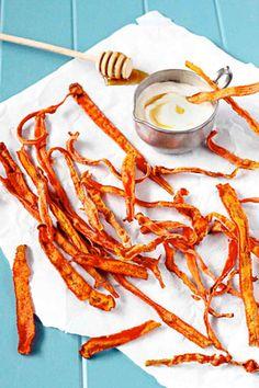 Вымытую, обсушенную и очищенную морковь нарежьте вдоль максимально тонко, сложите в миску и посыпьте корицей и имбирем. Сбрызните пергамент кулинарным спреем или оливковым маслом, разложите морковь в один слой и поставьте в духовку, разогретую до 200 градусов, на 10 минут.