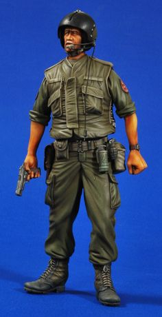 This figure of an airman in the USAF in the Vietnam era looks ready to take on the enemy even without his chopper! He wears of course his flight helmet and bullet proof flak jacket. He carries on his belt a smoke grenade/canister as well as a frag grenade and some spare ammo in a pouch with a water canteen. The airman also is wearing long boots with his combat pants tucked into them with a holster for the Colt.45 which he carries in his hand.