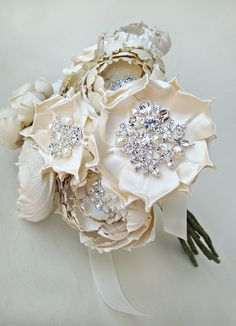 This silk fabric bridal bouquet is comprised of hand cut and formed silk fabric flowers of various shades of cream and ivory. Each flower has its own hand placed highlights featuring either rhinestones, crystals or genuine freshwater pearls. Completely handmade and stunning!Measures about 8 inches (20 centimeters) in diameter and 11 inches (28 centimeters) long.Takes many hours to complete this beauty.Each flower is its own individual piece with a green dupioni silk wrap...