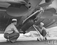 US Navy sailors loading a bomb on a Douglas SBD 'Dauntless' dive bomber. USA, 1942.