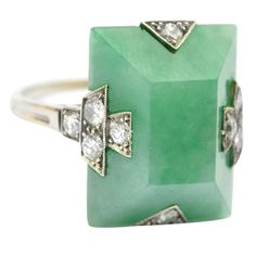 1920's Art Deco, platinum, jadeite, and diamond ring, set with a pyramidal table, with diamond melee accents. Signed BOUCHERON, #4978.