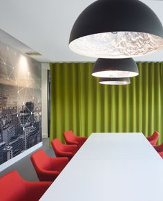 Meeting Room > Office interior design > How do you turn a meeting room into a stunning interior space? Answer: clever office design. This humble meeting space has a green partition curtain and bright red meeting room chairs which offer colour and contrast. The wall has a full sized photographic image covering the wall providing a landscape view from the inside, and the meeting room table is lit by three unusual pendant lights which are patterned on the inside.