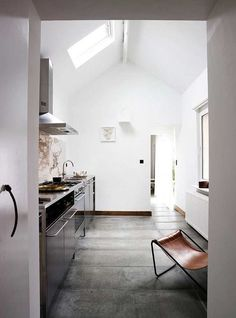 luminous white kitchen with skylights and concrete floor.