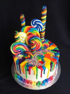 Rainbow drip cake with sprinkles and lollipops on white buttercream