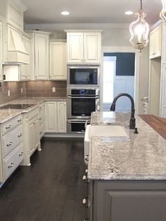white glazed cabinets, minka lighting, bianco antico granite, subway tile backsplash, gray kitchen island, kohler farm house sink, distressed hardwood floors, luxe homes and design