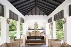 Impressive industrial steel beams support the pool cabana's ceiling, which shelters an outdoor kitchen, a teak dining table with a top made of lavastone is by Alfredo Custom Furniture.