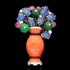 ART DECO 'TUTTI FRUTTI' JARDINIERE BROOCH BY CARTIER c.1930. Old single cut diamond brooch set with carved sapphire leaves, carved emerald flower heads, enhanced by cabochon rubies, black enamel all set in a carved coral vase,mounted in platinum.