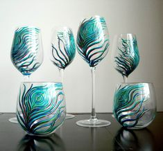 peacock glassware- this would be a great diy project. I think that the feathers should go all the way down the stem though.