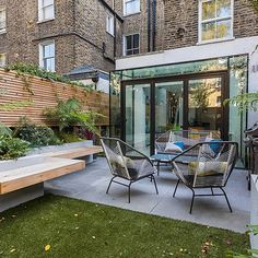 Small, contemporary garden in Islington, designed by Simon Ronan and constructed by The Garden Builders, flanking the terrace are raised beds, floating benches