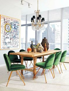 Gorgeous emerald-accented dining room with gold and green velvet dining chairs, a farmhouse wood table, modern graffiti art, and a crystal and gold chandelier.