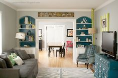 living // colored bookshelves, gray couch, yellow and teal