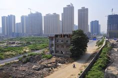 A man rides his bicycle past a partially demolished building in the middle of a street next to residential construction sites in Xi'an on August 14, 2013. According to local media, the owner of the house refused to move as a protest against a land-dispute lawsuit between him and his brother, which he lost.