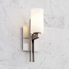This brushed nickel wall sconce features cylindrical frosted white glass for a softly diffused light.