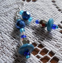 All Handmade, these cute, eye-catching earrings are made with Blue and Silver Colored Faceted Beads, Frosted Blue and Royal Blue Czech Glass E-Beads as well as Blue Swirl Disk Beads! Connected by fish/french hook wire