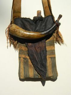 "This pouch is made from a piece of antique ticking. Lined with an extra layer of cloth for stability. The flap is brain tan deer skin. the horn is an original that has been patched with a leather ball up near the spout. the knife is also an original and has ""Peeled an awful lot of taters"" before it was re-purposed to go with the pouch. Strap is woven linen with an original buckle."
