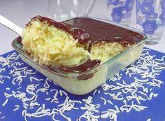 receita de cocada de travessa, com uma colherada sendo retirada da travessa, coberto com chocolate derretido