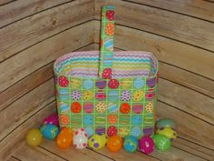 This Easter themed Fabric Basket is perfect for being filled with goodies from the Easter Bunny. The exterior fabric has multi-colored Easter Eggs in blocks on a green backround. There is glitter all over the fabric. The coordinating lining fabric has multi-colored rick-rack stripes. There is a single handle across the center of the basket for easy carrying.  Your basket can be personalized! Add a name across the front of the basket! Choose a font from the last photo and the color thread you…