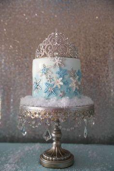 O bolo de formato simples ornamentado com delicados flocos de neve consegue parecer muito mais chique graças à coroa de princesa no topo e ao belíssimo suporte com cristais. Prova de que, para seguir no tema da festa, nem sempre é preciso usar os personagens do filme explicitamente, apenas fazer referência a eles.