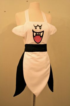 "Neil Grey's Etsy shop, Dark Balloons, has several geeky aprons available, my favorite of which is this Boo one. There're magnets in the arms and eyes so you can have Boo ""hide"" just like it would in the games! There's also Link and Zelda a la Spirit Tracks, Princess Peach, and all three of the Powerpuff Girls-inspired aprons as well."