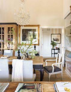 Vista del pasillo desde el comedor, con mesa y sillas, chandelier, cuadros y mesita velador