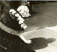 Jean Harlow signing her name in the cement at Grauman's Chinese Theatre in Hollywood.