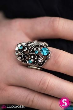 Brushed in an antiqued finish, metallic petals swirl into a romantic floral bouquet that is sprinkled in glittery blue rhinestones.   Sold as one individual ring.