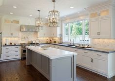 Kitchen Design. Gorgeous kitchen with white perimeter cabinets paired with honed black countertops and white marble backsplash. Worlds Away Mariah Pendants over gray kitchen island with white marble countertop with prep sink accented with gooseneck faucet. #Kitchen #Design #KItchenDesign Blue Water Home Builders.: