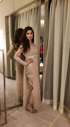 Mahira Khan in an outfit featured by Élan at the PFDC Swarovski Crystal Couturiers. Originally paired with a skirt, she added her distinctive touch by pairing it up with cigarette pants. From the pale taupe outfit encrusted with embellishments, to the studded silver strap belting the duppatta and the matte silver stiletto to the pearl earrings, everything exuded grace.