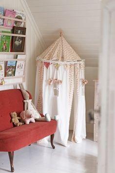 Den røde sofaen skaper en stilig kontrast og setter en herlig prikk over i-en i det ellers så harmoniske barnerommet.