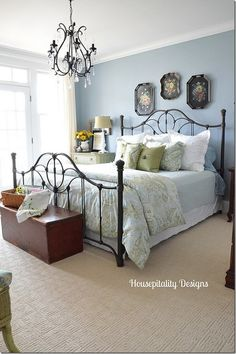 Love the touches of black in this guest room ~ black iron bed, black chandelier  the black tole painted trays above the bed.