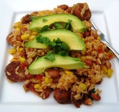 Arroz Antioqueno     1 cup white rice     2 ½ chicken stock     ¼ cup chopped white onions     1 scallion, chopped     1 medium tomato, chopped     ¼ cup chopped red bell pepper     1 garlic clove, chopped     1 tablespoon olive oil     2 chorizos, sliced     ¼ pound bacon, cut into small pieces     ½ cup frozen corn     1 (15.5 oz) can pinto beans     1 sweet plantain, peeled and diced     1 tablespoon butter     ¼ cup fresh cilantro, chopped     Avocados for serving     Salt and pepper
