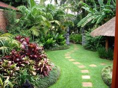 Tropical Garden - stunning, just need to render or paint that brick wall a charcoal colour or match the stone gateway