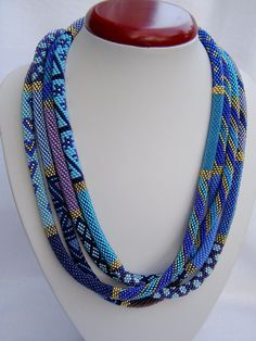 Bead crochet patterns in various shades of blue with gold accent.