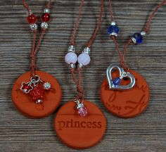 These fun necklaces feature hand stamped designs on a 1.25 diameter disk of terracotta clay. Finished with silver embellishments and