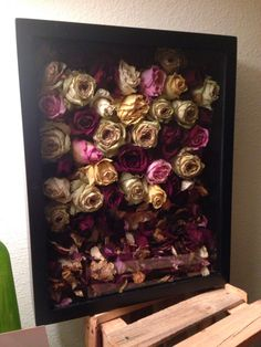 Keepsake shadow frame. Engagement  or wedding roses. Dry out and then cut at base of stem. Hot glue them to a cardboard backing. Use loose petals to fill any space.