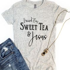 "This is a super-soft fitted ladies tee with our ""Raised On Sweet Tea & Jesus"" design. Fit: Women's & runs slightly small. *Heather grey with black text"
