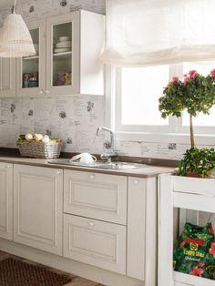 Cocina en color blanco con fregadero con escurreplatos delante de la ventana