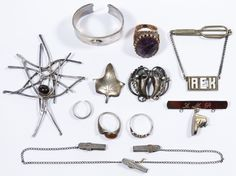 """Lot 556: Modernist Sterling Silver Jewelry Assortment; Including sterling silver pins, rings and clips, most marked """"sterling"""" or """"925""""; together with a ring having an oval cut amethyst and a napkin ring having two fish design"""