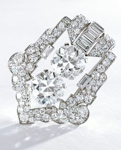 PLATINUM AND DIAMOND CLIP-BROOCH, CARTIER, CIRCA 1925. Of open work, geometric design set in the center with 2 old European-cut diamonds weighing 6.07 and 5.99 carats, further set with baguette and old European-cut diamonds weighing approximately 5.95 carats, signed Cartier, numbered 37-16799.