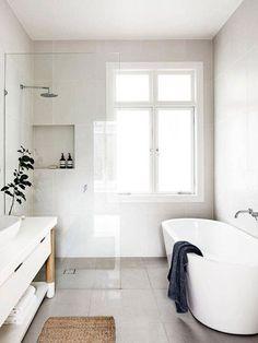 Baño de color blanco con ventana, luz natural, ducha y bañera.