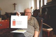 """Sr. Mary Ellen Howard, RSM, former executive director of the St. Frances Cabrini Clinic in Detroit, holds a sign highlighting the Jubilee Year of Mercy.  The sign reads, """"Become a door of mercy through which those who enter may experience the love of God."""" (Dan Meloy 